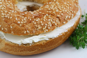 Bagel with cream cheese with watercress garnish, close up