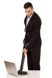 serious and attractive young businessman vacuum cleans his lapto