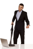 smiling and attractive young businessman vacuum cleans his lapto