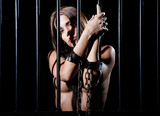 nude or naked woman behind prison bars and cuffed