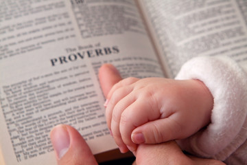 Baby Holding Dad's Finger on Bible