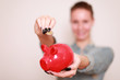 Frau wirft 2 Euro in roten Sparschwein