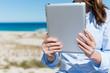 frau liest mit tablet am strand