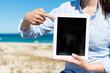 frau am strand zeigt auf tablet-pc