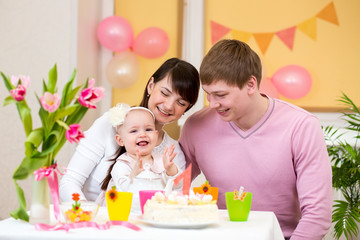 family celebrating first birthday of baby daughter