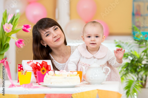 Little girl and mother celebrate birthday holiday. Focus at baby