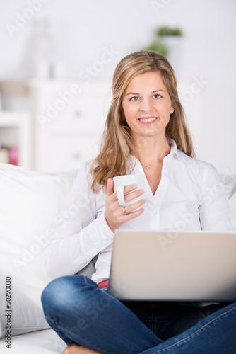 frau sitzt mit kaffee und laptop auf dem sofa