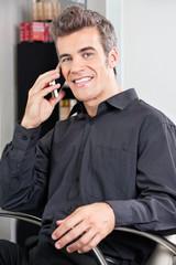 Male Customer Using Cellphone At Salon