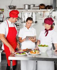 Chefs Using Digital Computer In Kitchen