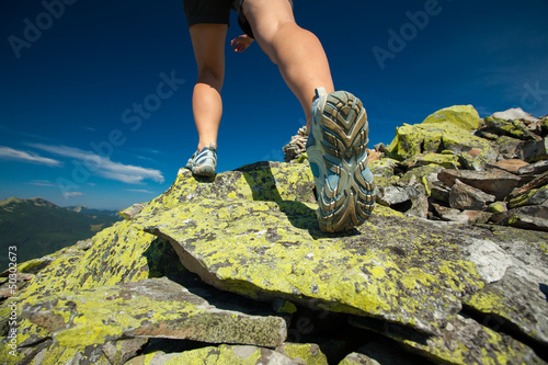 Hiker jumps over stones in Carpathian mountains with foot closeu
