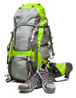Hiking shoes and packed backpack on white background