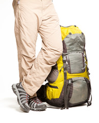 Man stands near packed backpack and ready to go