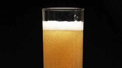 Bottle filling a glass of beer on a black background