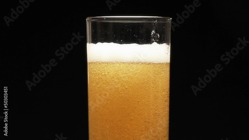 Bottle filling a glass of beer on a black background