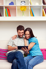 young couple looking at the tablet pc