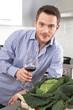 Mann trinkt in der Küche ein Glas Wein