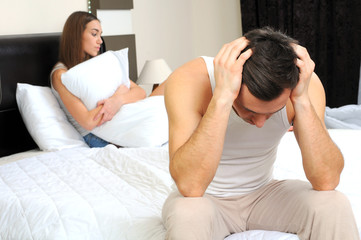 Upset man sitting on the bed with his girlfriend
