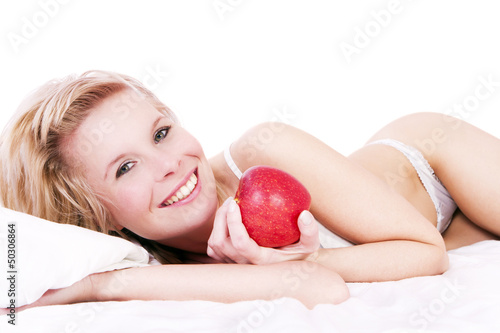 Beautiful blonde girl lying on the bed, holding apple.