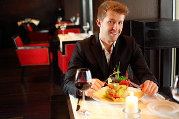 Happy young man in black suit in a restaurant