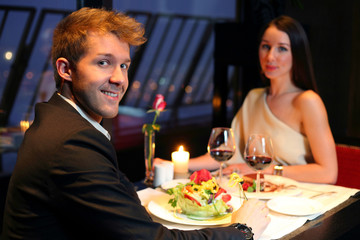 A young boy and a beautiful girl having dinner