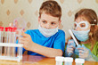 Boy fills chemical test tubes with specimen and girl