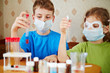 Boy and girl sit at table with chemical reagents and look
