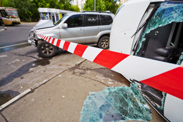 Place of car accident fenced with barrier tape