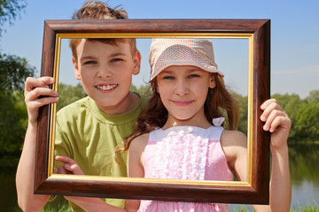 Smiling girl and boy stand outdoors, holding picture frame