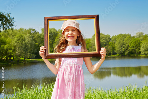 Girl stands in grass on bank of pond with her eyes closed
