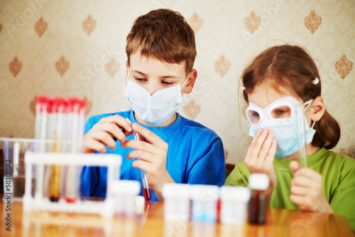 Boy fills chemical test tube with specimen and girl sits near