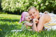 Young mother and her baby snuggle their cheeks, sitting on grass