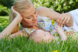 Smiling young mother reclines on green grass next to her baby