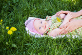 Mother hands touch her baby, that lies on grass