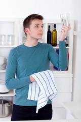 man drying and polishing glass with a kitchen towel
