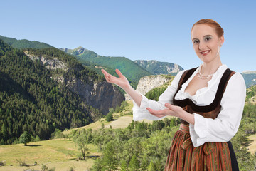 Frau im Dirndl präsentiert Bayern mit Hintergrund Berge