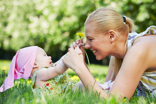Young smiling mother plays with her baby on grass in spring park