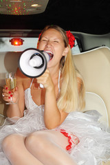 Young beautiful bride sits in car, holds glass of champagne