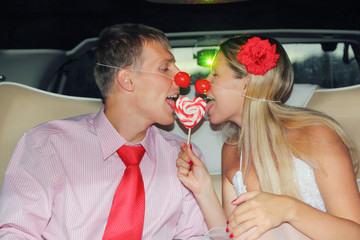 Young bride and groom with clown noses sit in car