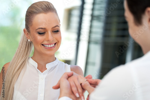 Cute girl being surprised with diamond ring.