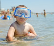 Small boy wearing goggles at the seaside