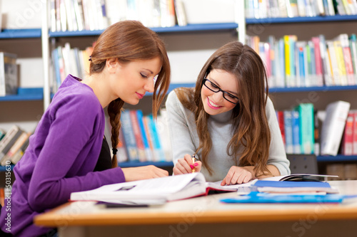Two pretty college students in a libray