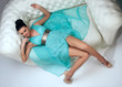 girl in a turquoise dress lying on sofa