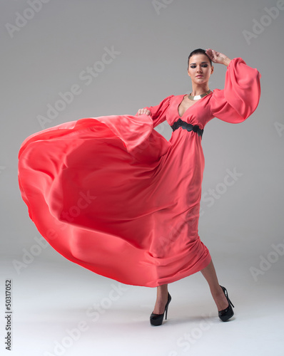 girl in a long red dress dancing