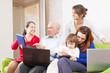 family enjoys in livingroom room with few laptops
