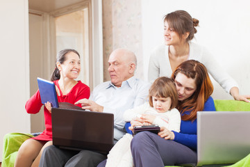 family enjoys in livingroom room with few laptops