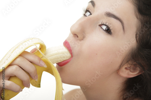 Beautiful sexy woman eating banana on white background