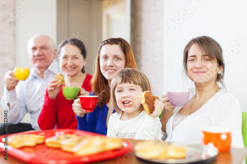 Happy family drinks tea with cakes