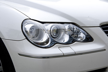 The headlight of a white car parking beside the road.