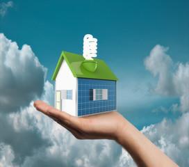 Casa con paneles solares y bombilla en la mano