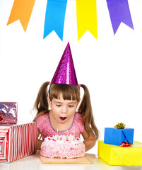girl blowing candles on her cake. isolated on white
